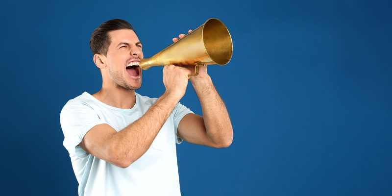 Handsome Man With Megaphone On Blue Background. Fighting With Co